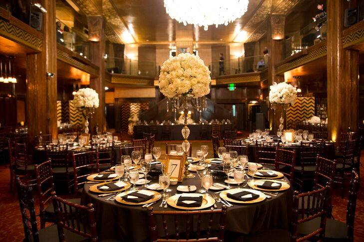 Reception dining tables were set with black linens and gold dinnerware, surrounding the tall centerpieces filled with ivory roses and hydrangeas created by Lavenders Flowers.