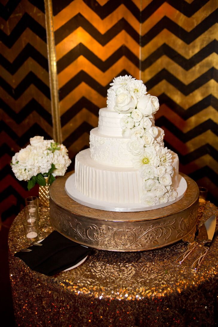 The four-tiered ivory wedding cake was designed by Joanie & Leigh's Cakes, accented with ivory roses and daisies.