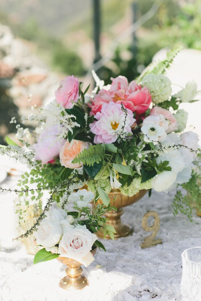 """Megan from Honey & Poppies created a series of textured, full arrangements of dahlias, peonies, garden roses, ferns, lilacs and hydrangeas in shades of pink, ivory and peach that brought the reception tables to life. """"Flowers really add a big romance factor to a wedding's atmosphere,"""" Sarah says."""