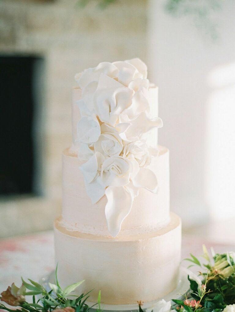 White three-tier wedding cake with white flower decorations