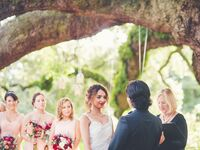 Couple with officiant during wedding ceremony.