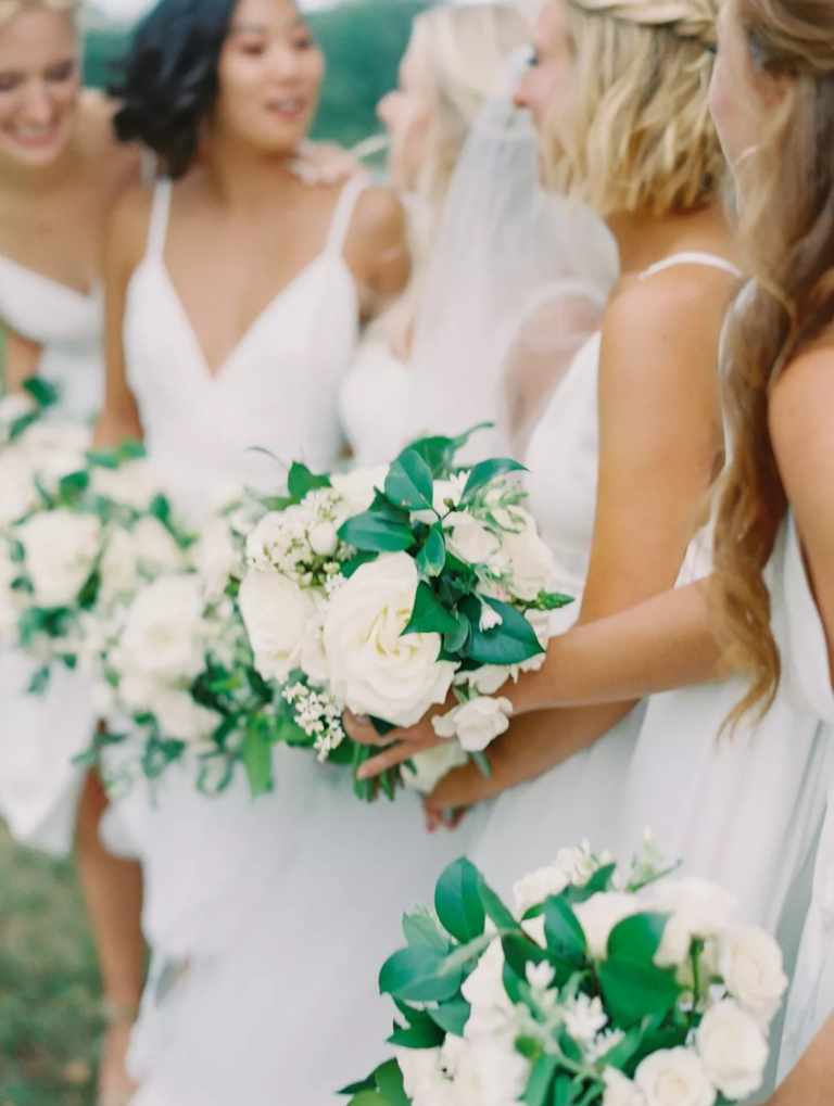 Bridesmaids in white dresses with white-and-green bouquets