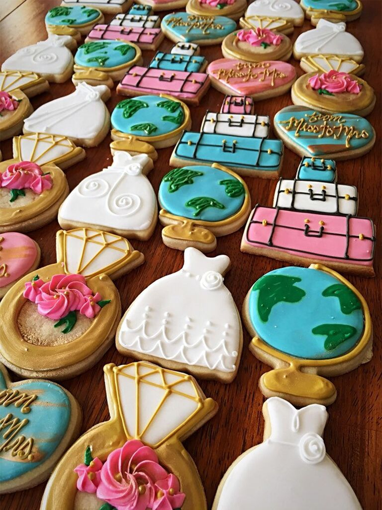 Cookies decorated colorfully as globes, wedding dress, wedding ring, luggage, etc.