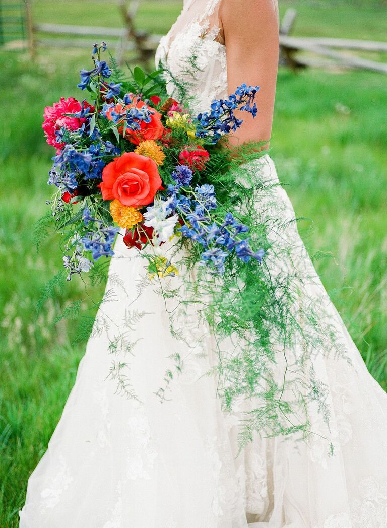 bride holding red bouquet with cascading greenery