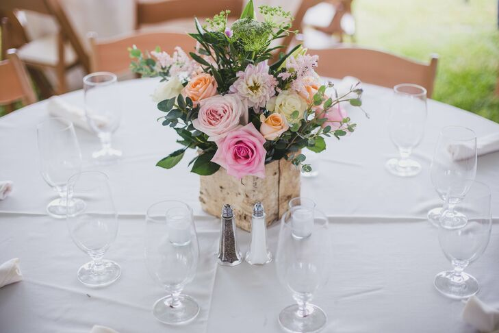 """The dining-table centerpieces incorporated roses, dahlias, astilbes, Queen Anne's lace and greenery in a rustic, wood-covered box. """"We had pretty simple decorations because we didn't want to take away from the beauty of the venue,"""" the bride says."""