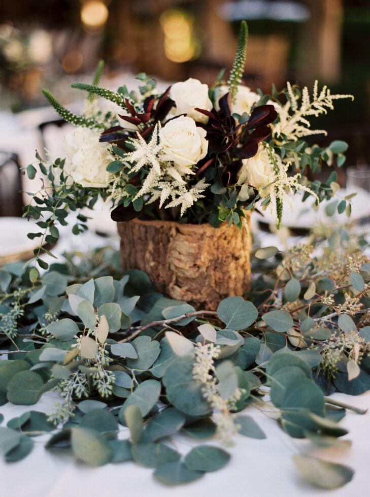 Dining table centerpieces of white astilbe and roses with burgundy leaves in distressed wooden boxes on a bed of silver-dollar eucalyptus created a fall woodland atmosphere at the reception.