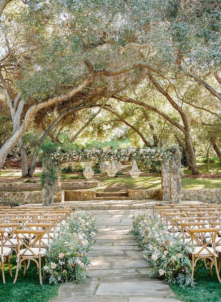Wedding ceremony with stone arch and wood chandelier decorations