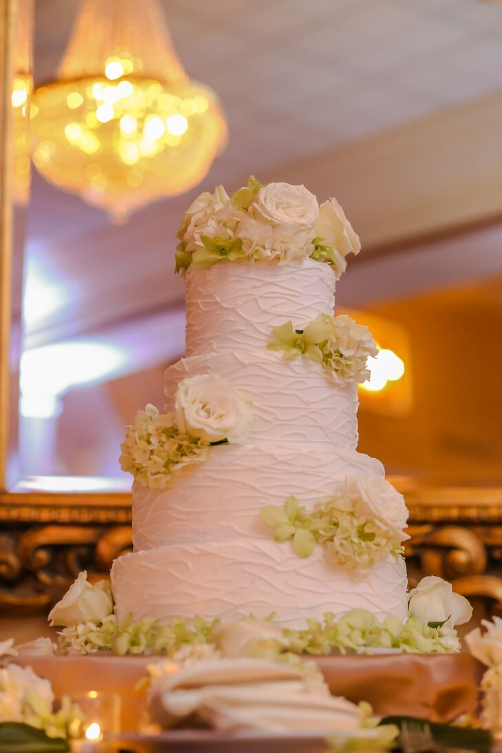 """Chantilly Cakes baked Alina and Nick a classic white wedding cake with a fun twist. Each tier was composed of either red velvet or funfetti cake as a piped design, green hydrangeas and white roses decorated its white icing. """"I think the cake cutting just showed the silly, real side of Nick and I,"""" says Alina. """"Especially when I went straight for his face with the cake. No holding back."""""""