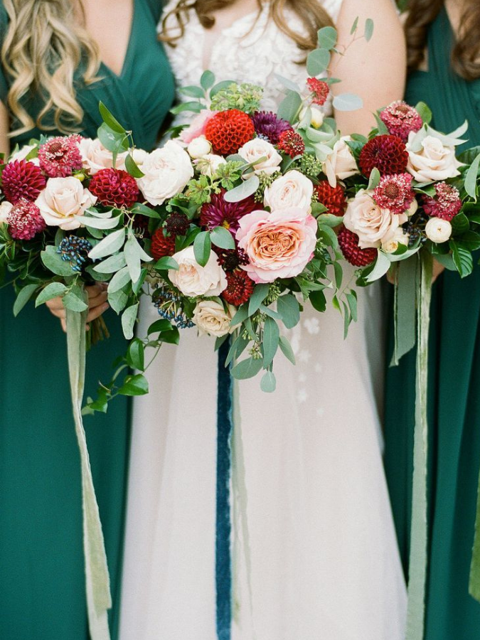 Bridesmaids in green dresses holding red dahlia bouquets