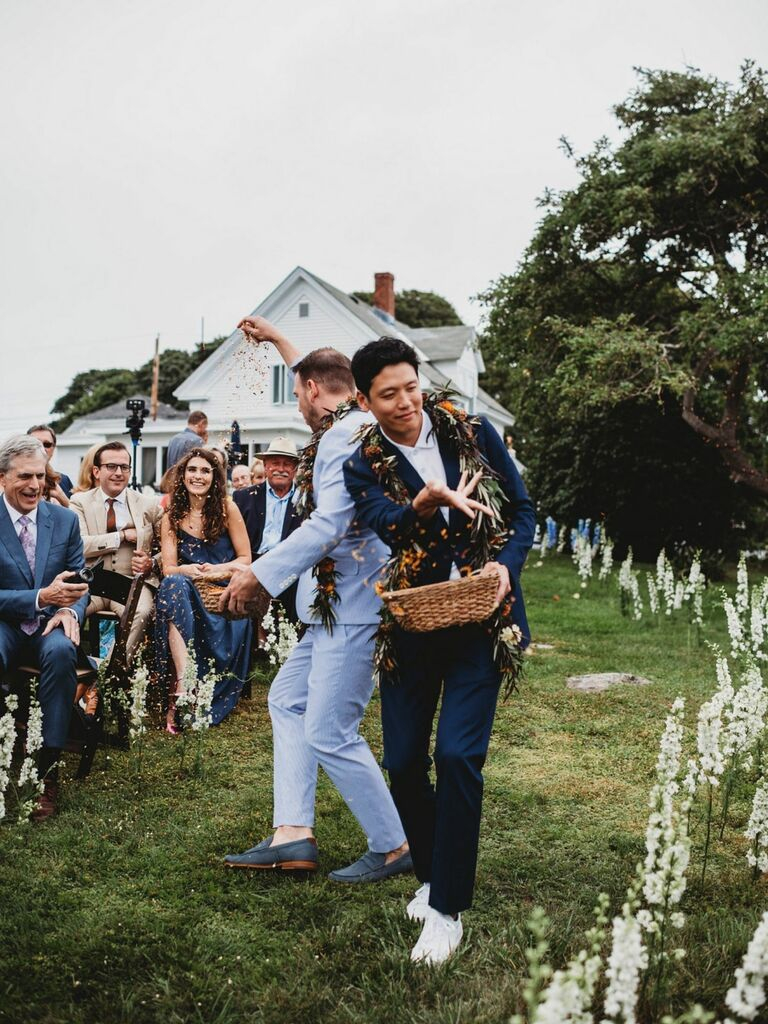adult men tossing flower petals down the aisle