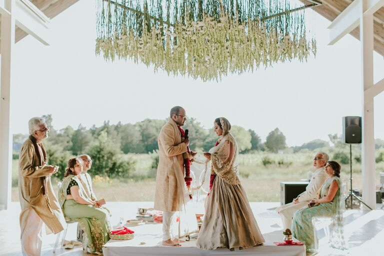Couple under modern mandap with hanging flowers