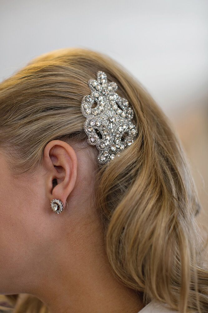 The bride went a little retro with an old-fashioned sequin comb to complete her old Hollywood glam look. She wore her hair down in big curls pinned to one side by the comb.