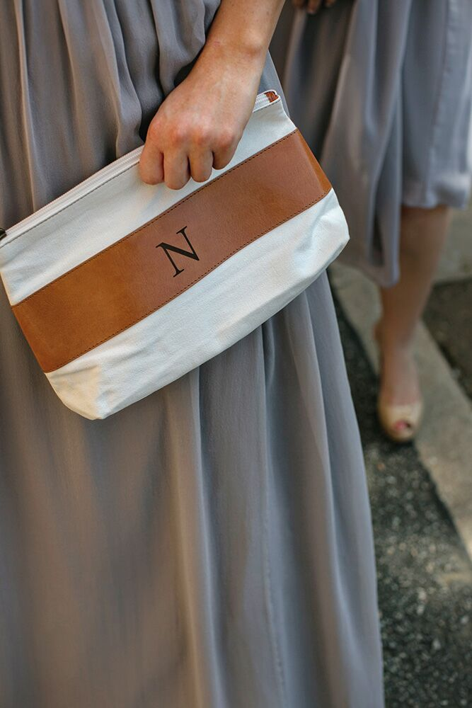 The bride gave each of her bridesmaids her own makeup bag with a monogrammed initial to carry her makeup for the ceremony.