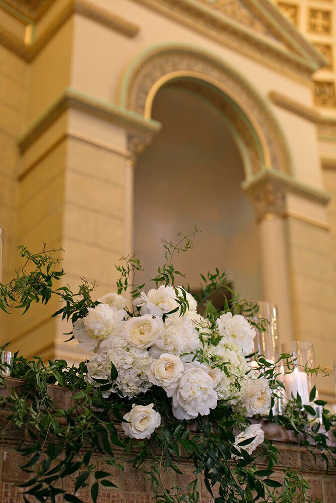 The Pasta's decided on lush and trailing floral swags composed of white peonies, white hydrangea and white garden roses accented with jasmine to adorn the ledges at the back of the altar area. Clear glass cylinders in varying heights with pillar candles were scattered among the flora.