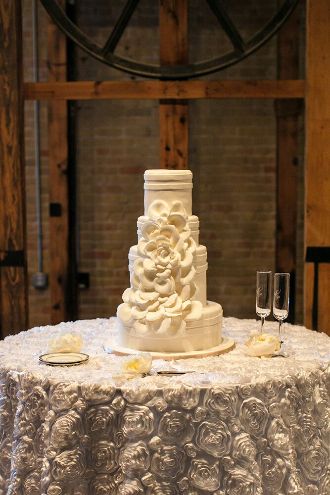 """A simple, classic tiered white buttercream cake with cascading flowers was exactly what the bride wanted. """"I was actually shocked by my decision to have a strawberry cake [with strawberry icing between the layers], but Simon Lee's was delicious and gave a pop of color to the all-white decor,"""" says Paige."""