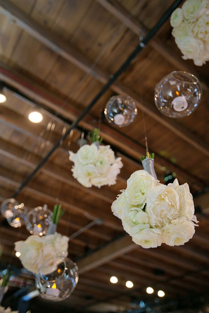 Chic clear glass globe candleholders were suspended by the overhead beams of Brazos Hall at varying heights. Following the ceremony, the bridesmaid bouquets were also suspended from the beams.