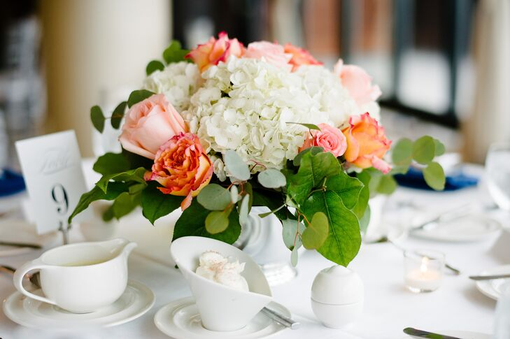 Coral roses and textured greenery added a splash of fresh color to the reception tables.