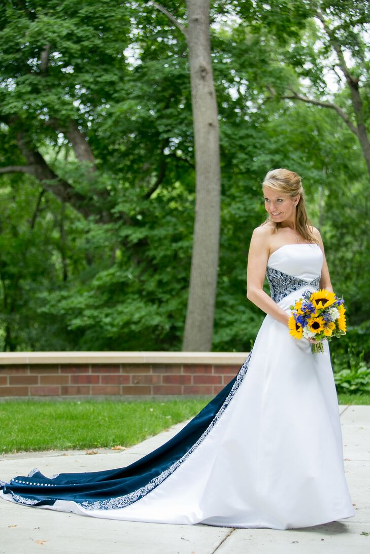 """Dawn wore a strapless wedding dress with a navy band around the waist and down the train. """"We had already chosen a deep blue for the bridesmaid dresses, so when I saw this dress at Classy Consignments Bridal, it was perfect,"""" Dawn says."""