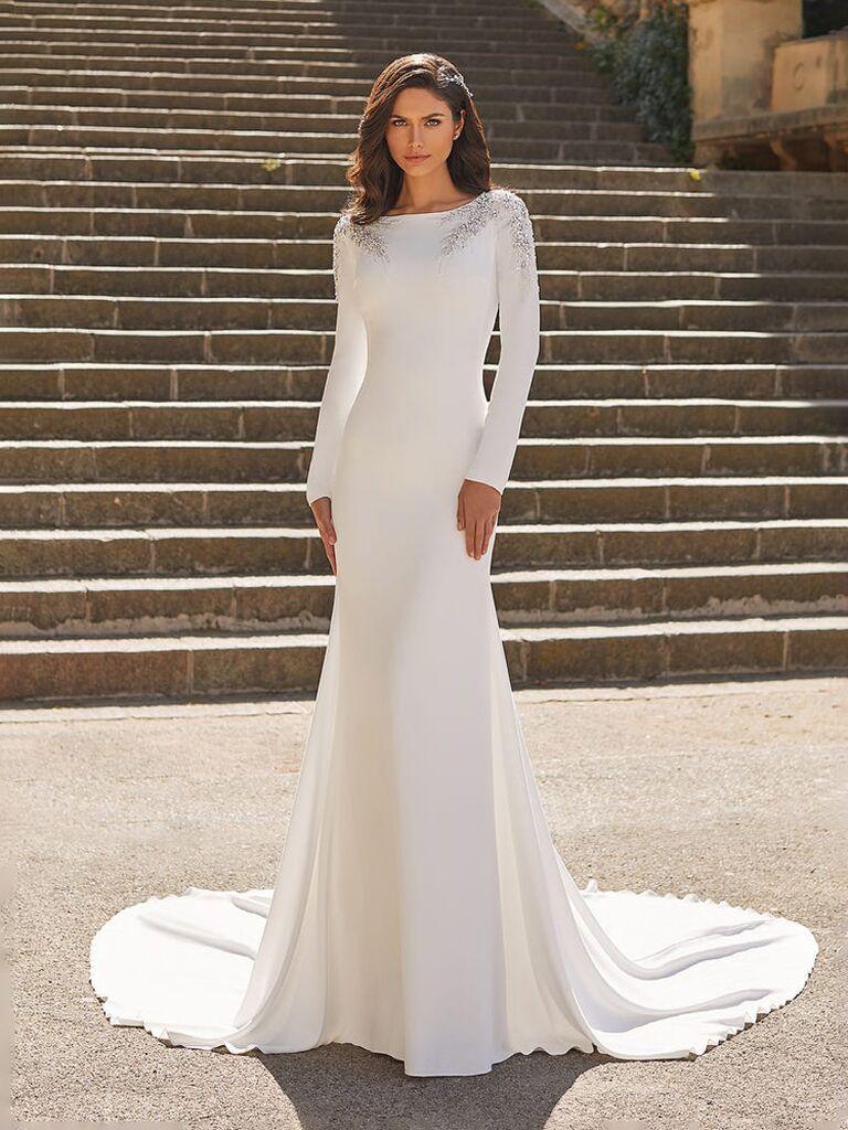 Áo cưới màu trắng của pronovias với tay áo dài cổ cao với phần vai xếp nếp xuống phía sau ngực trơn và dạng trơn phù hợp với váy hoa xếp nếp váy cưới đơn giản đẹp