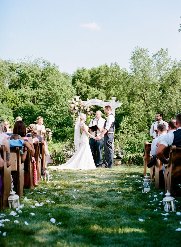 The ceremony arbor was placed in front of a group of trees. The aisle was decorated with white rose petals and lanterns.