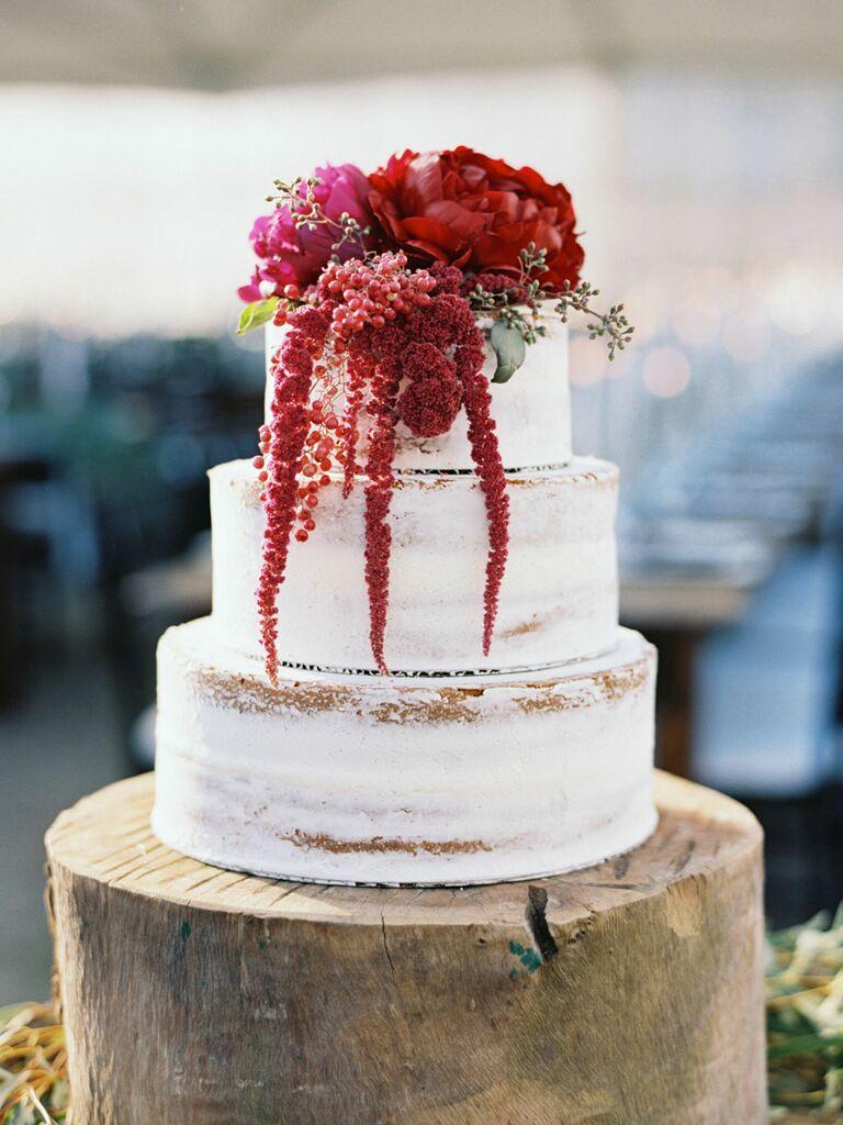 Rustic semi-naked three-tier wedding cake with crimson flowers