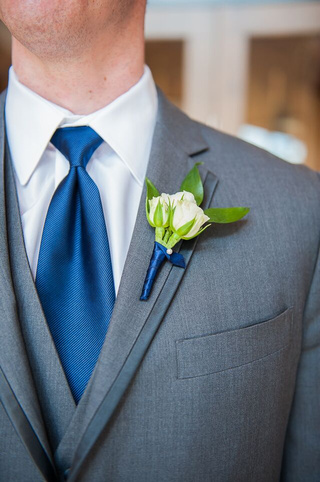 Alex's groomsmen paired their gray suits with two navy accents. They wore navy ties and tripled white rose boutonnieres wrapped in navy ribbon.
