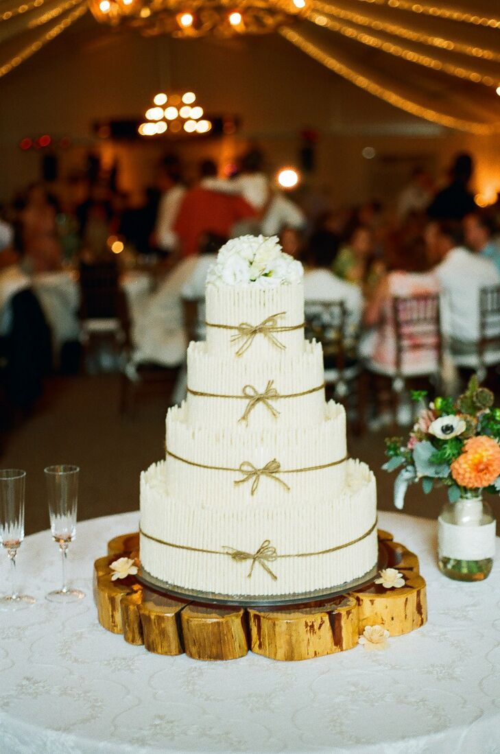 The four-tier buttercream cake was decorated with textured white chocolate sticks and accented with a twine bow on each layer.