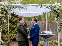 Grooms exchanging vows under chuppah at Jewish wedding ceremony