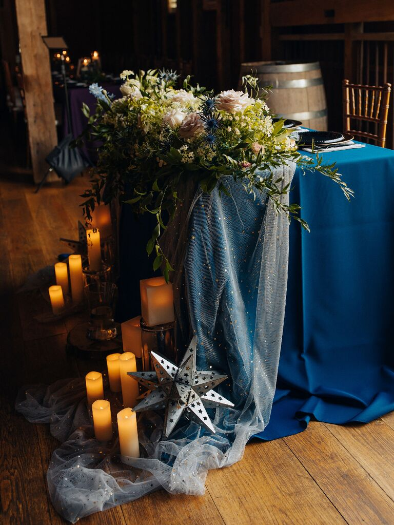 Celestial wedding decorations covering sweetheart table with table runner and candles at zodiac wedding