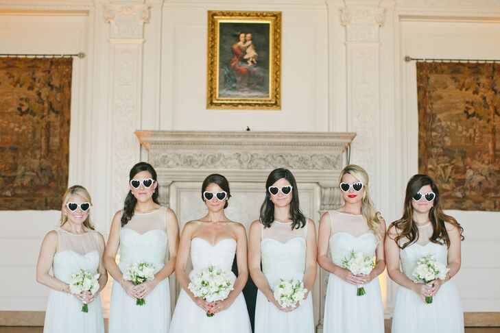 Playing off her own wedding day look, Margot chose a floor-length gown by Amsale with an illusion sweetheart neckline and A-line silhouette for all of her bridesmaids. The ivory hue and elegant styling lent their look an ethereal feel without compromising on formality.