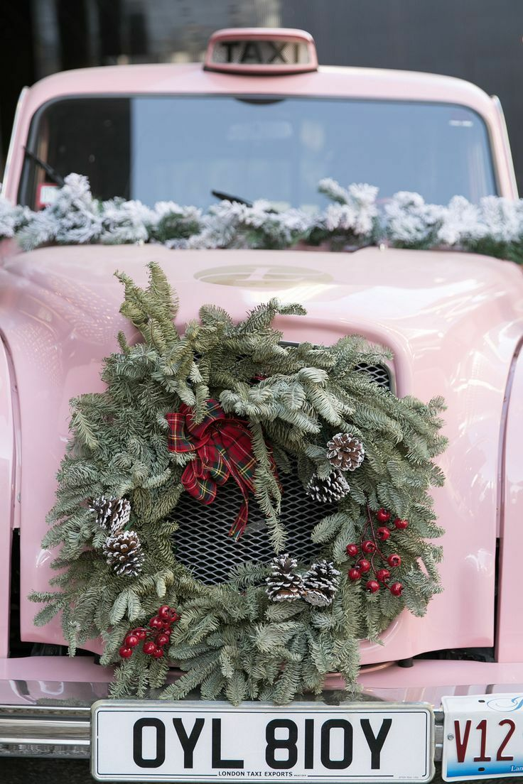 Pink vintage car decorated with green wreath