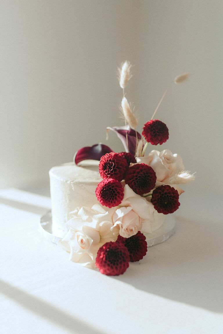 One-tier cake with fresh burgundy dahlia and cally lily blooms.
