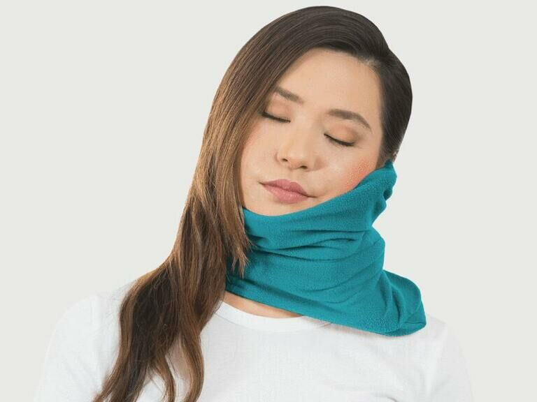 Woman wearing cozy neck pillow for travel in blue