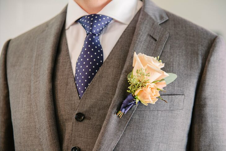 Simple boutonnieres of peach roses were tied together with a navy ribbon.