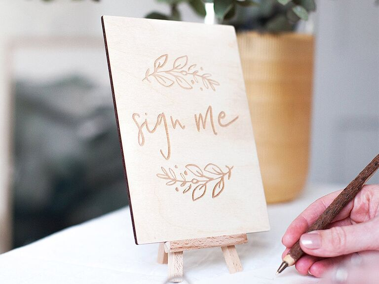 'Sign me' engraved in wooden sign with vine designs