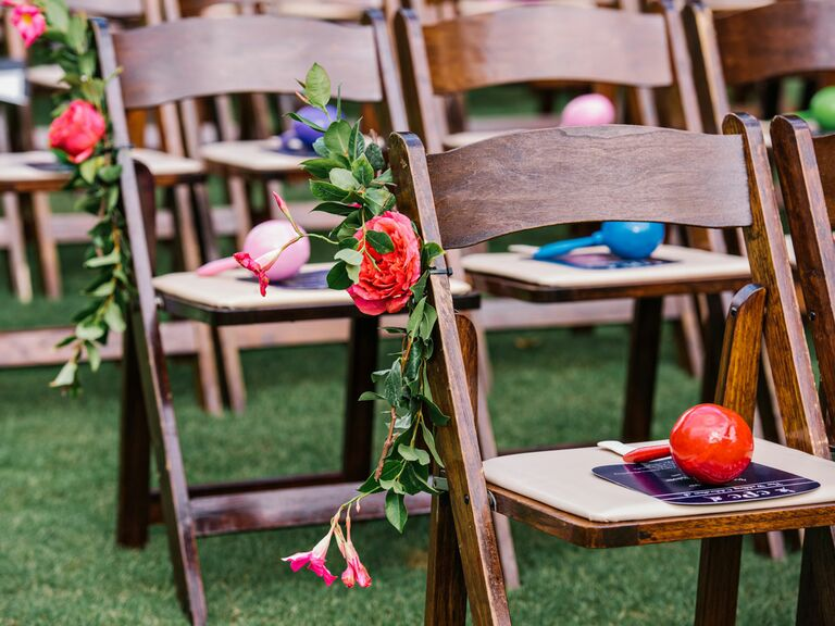 Wedding ceremony seating with bright florals and maracas