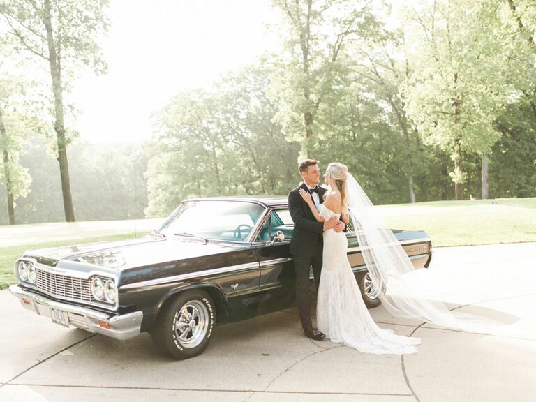 Bride and groom in front of black vintage getaway car