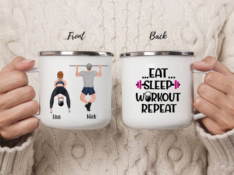 White mug with graphics of couple working out and names, 'Eat, Sleep, Workout Repeat' in black type on the back
