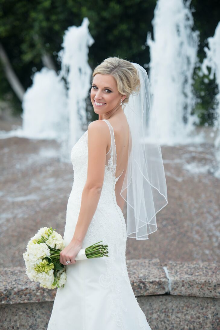 Brianna's dress was absolutely stunning! She wore a sleeveless ivory trumpet-style wedding dress with lace appliques, an illusion neckline and a plunging back lined with buttons.
