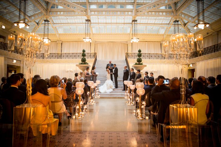 """Emily and Tyler immediately fell in love with the Rookery—a historic landmark in the heart of Chicago's financial district—from the moment they set foot inside the building. """"We held our wedding in the light court, which features white marble and wrought-iron staircases,"""" Emily says. """"We wanted to incorporate as much of our venue into our design as possible."""""""
