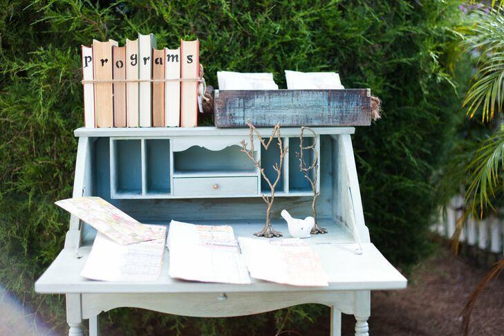 Programs were displayed on a pale blue vintage secretary's desk accented with rustic details such as antique books and twigs in the shape of the couple's initials.