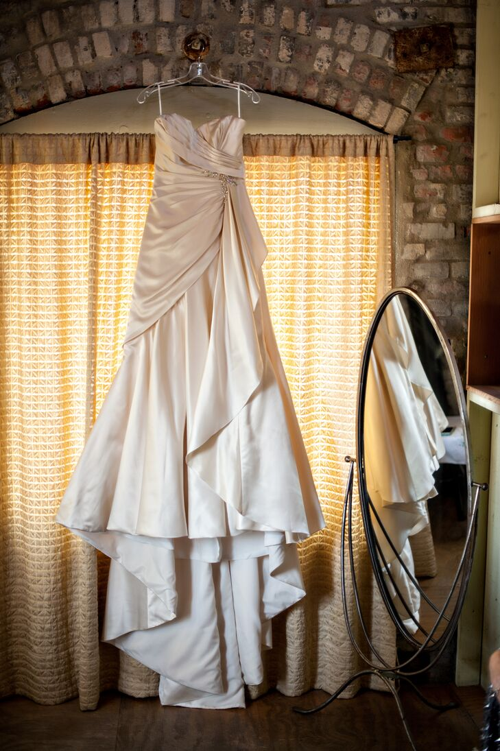The bride wore a strapless ivory wedding dress on her wedding day, with elegant drapery going down the skirt of the gown.