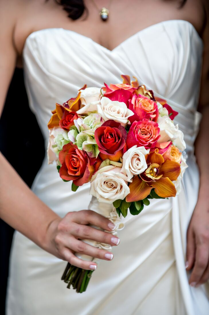 Rose held a red, burnt orange and ivory colorful bouquet made up of roses and lilies.