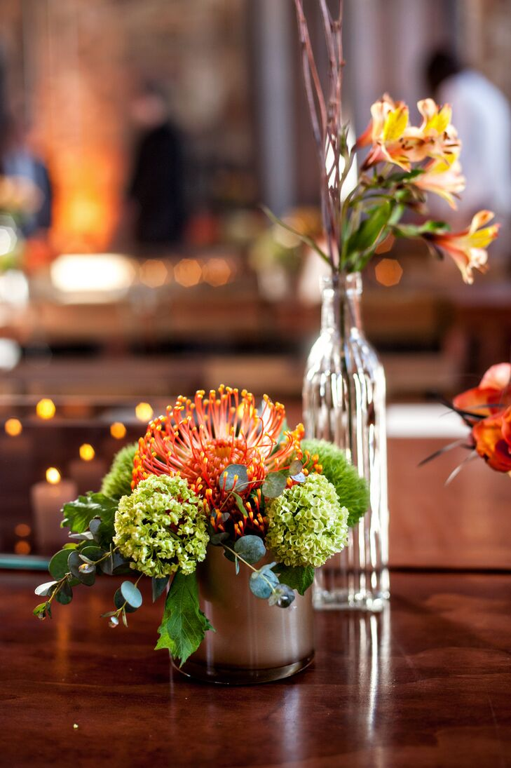 On reception tables, green and orange succulent arrangements as well as lilies mixed with branches in a glass bottle served as centerpieces.
