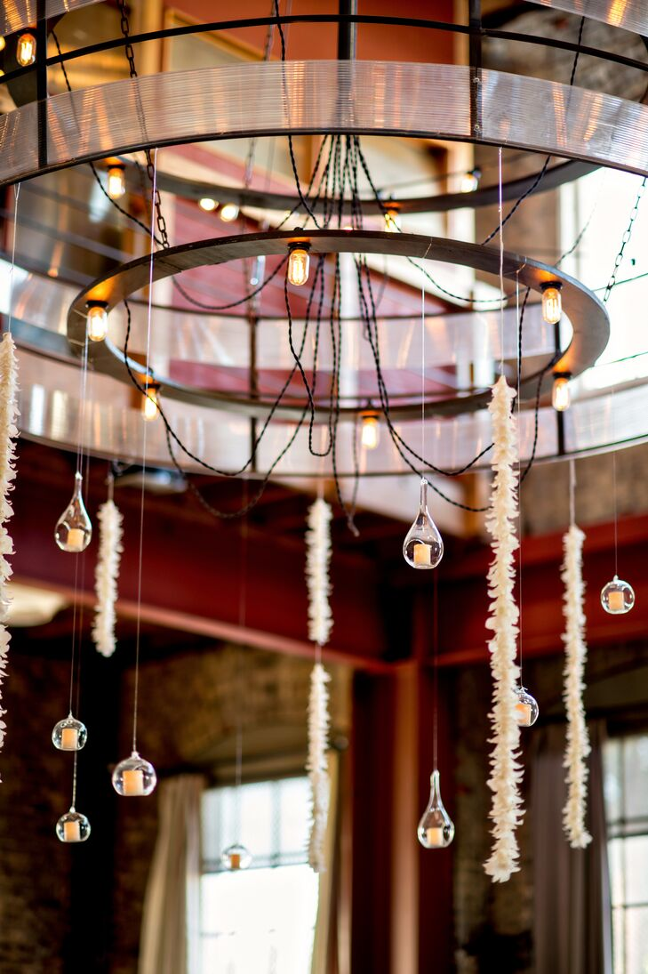 The chandelier inside the venue had teardrop glass pieces with candles and long flower arrangements hanging from its wooden circular shape.