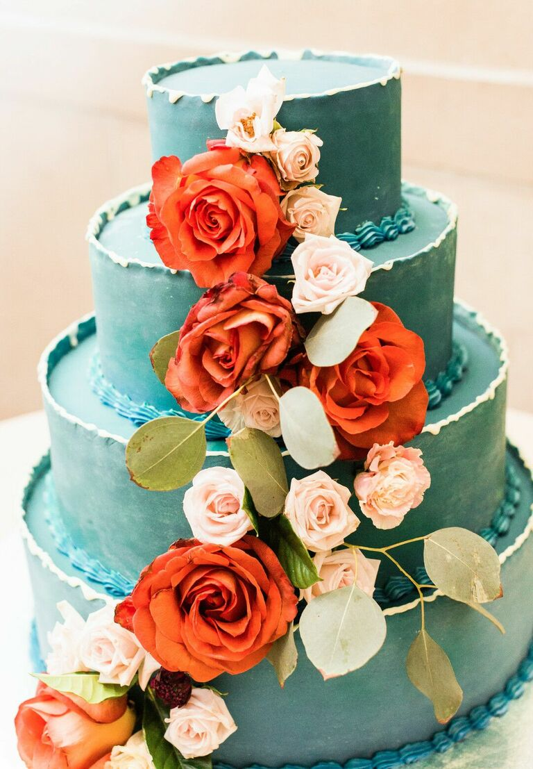Four-tier teal cake with fresh red roses