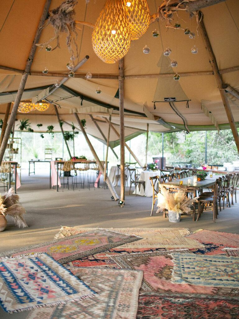 Bohemian tented wedding reception with colorful layered rugs and macrame hanging lights