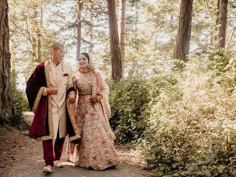 Couple holding hands smiling in forest