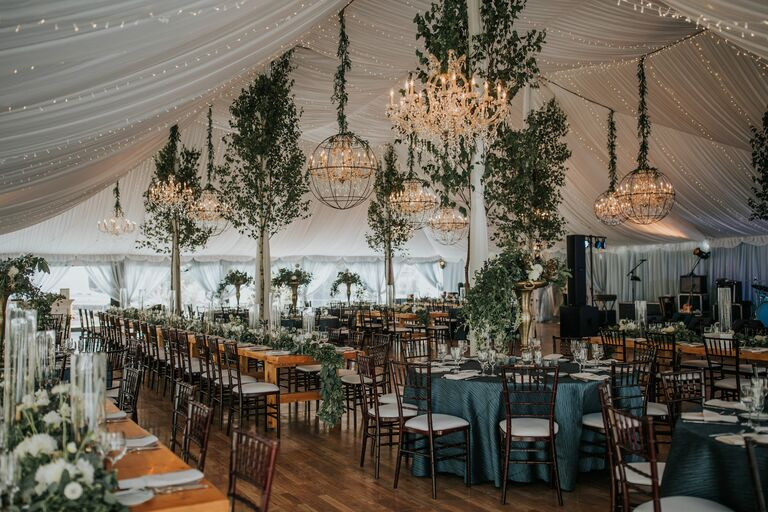 Tented reception with chandeliers and tree decorations