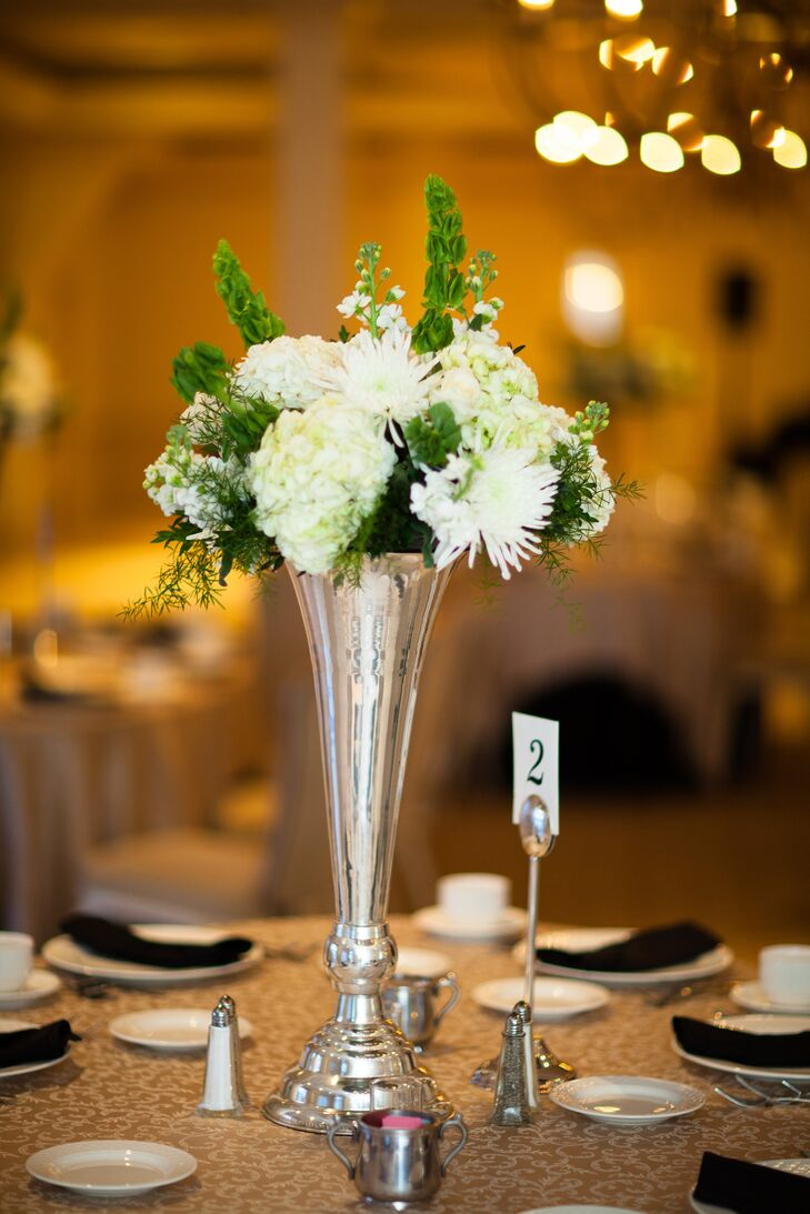 """The couple decorated their reception with gold linens, black napkins and silver trumpet vase centerpieces. Each arrangement included white hydrangea, bells of Ireland and white chrysanthemums. """"The centerpieces included bells of Ireland in honor of the bride's Irish heritage and her Grandmother,"""" says Cara."""